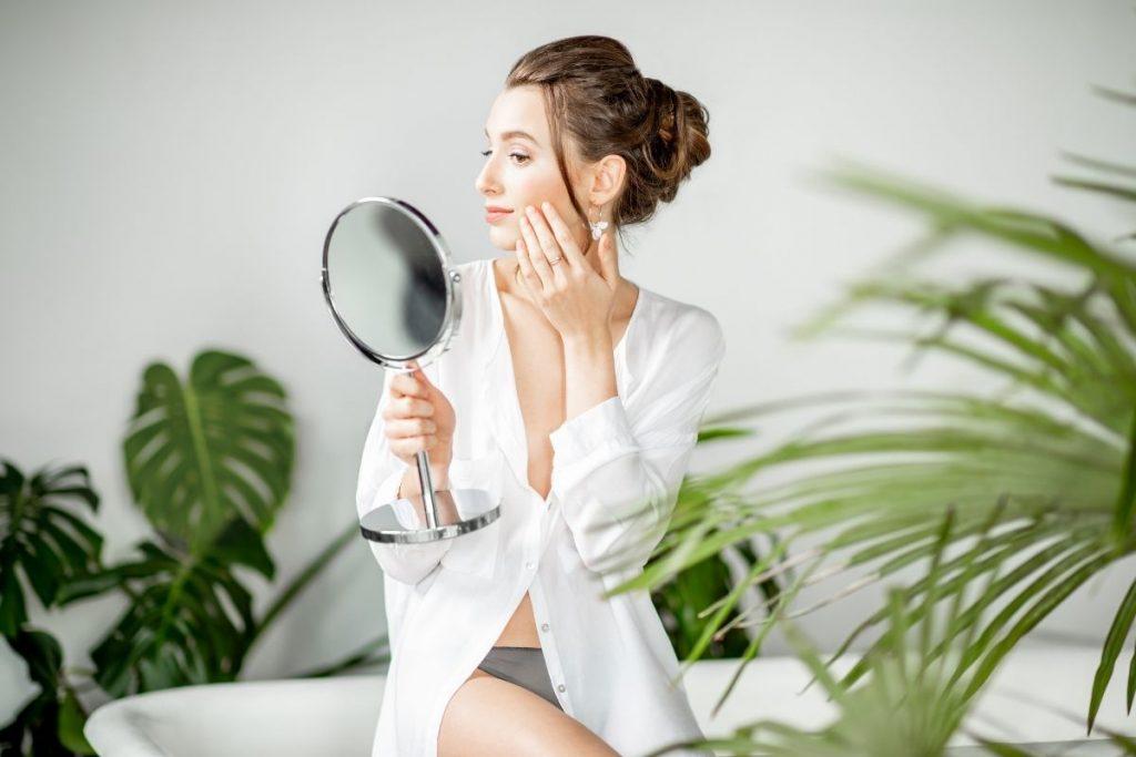 Kobieta oglądająca efekty zabiegu medycyny estetycznej, wykonanego w krakowskiej Klinice Genesis