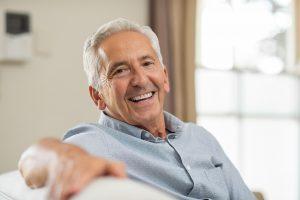 Demencja i Alzheimer - starszy zdezorientowany mężczyzna trzymający się za głowę.